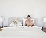 Man Lying in Bed Next to Skeleton