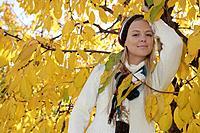 Woman Standing Amongst Fall Leaves