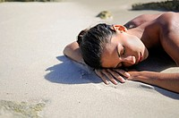 Young attractive woman sleeping on the beach