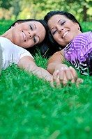 Two smiling sisters lying outdoors in grass holding hands