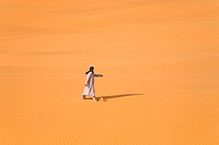 single bedouin walking over a sand plain in the Libyan desert, Libya, Sahara