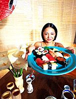 Woman Offering Plate of Sushi