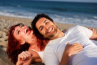 Young couple at the beach laughing