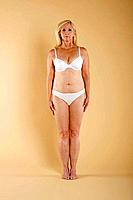 Full length of a semi nude woman in white lingerie