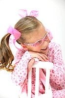 Pretty blond girl with pink glasses sitting on a chair