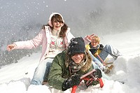 three teenagers frolicly tobogganing at a snow_covered mountain slope