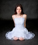 Girl in a white dress sits on a black background