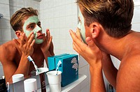 Young man doing face care