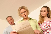 shocked parents looking at the phone bill, daughter standing with them