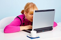 Young girl _ is looking closely at laptop monitor