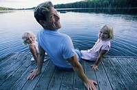 Father Sitting with His Two Daughters on Jetty