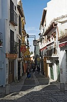 Narrow street with shops and restaurants in Albaycin, Granada, Spain