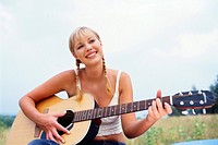 Young Woman Playing Guitar in Meadow