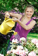 woman watering plants in garden