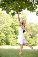 woman reaching up to branch