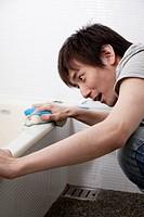 Young man scrubbing bathtub