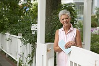 Senior Woman Standing at Garden Fence