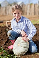Girl picking gourd in garden