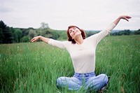 Mature Woman Sitting in Field with Arms Outstretched