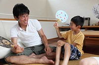 Father and son holding fan and playing