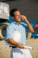Architect Holding Blueprints and Talking on a Cell Phone at a Construction Site, York Region, Ontario