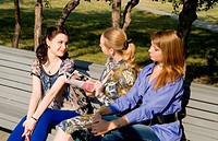 Three girls discuss magazine on the branch