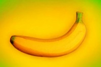 A ripe yellow banana on a yellow background