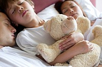 Boy sleeping in bed with his parents, holding teddy bear
