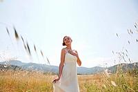 Bride wearing wedding dress alone in field