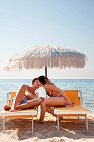 Young couple on sun loungers kissing