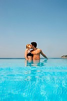 Young couple kissing in infinity pool (thumbnail)