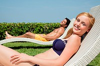 Young couple on sun loungers