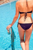 Young woman on swimming pool steps, rear view (thumbnail)