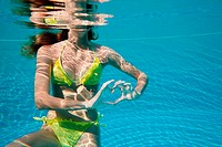 Young woman making heart shape with hands underwater in swimming pool