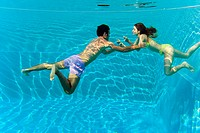 Young couple swimming in swimming pool, underwater view