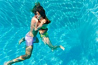 Young couple embracing in swimming pool, underwater view