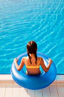Girl with inflatable ring by swimming pool