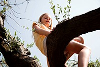 Girl sitting on tree branch, low angle