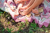 Children lying barefoot on patchwork blanket, low section