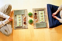 Young couple sitting on the floor eating sushi