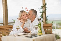 Couple in bathrobes kissing at breakfast
