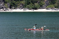 Two young women kayaking at Monkey Island off Cat Ba Island Halong Bay Vietnam