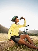 Mixed race biker taking a break and drinking water