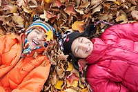 Young boy and girl playing with Autumn leaves