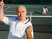 Mature Tennis Player Clenching His Fist on Court