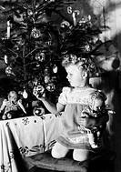 Christmas, distribution of presents, little girl beside a Christmas tree, 1940,