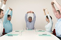 Businesspeople Stretching at Conference Table