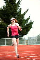 Mixed race teenager running on track
