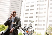 Black businessman sitting on scooter talking on cell phone