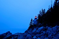 Glowing lighthouse on rocky shore